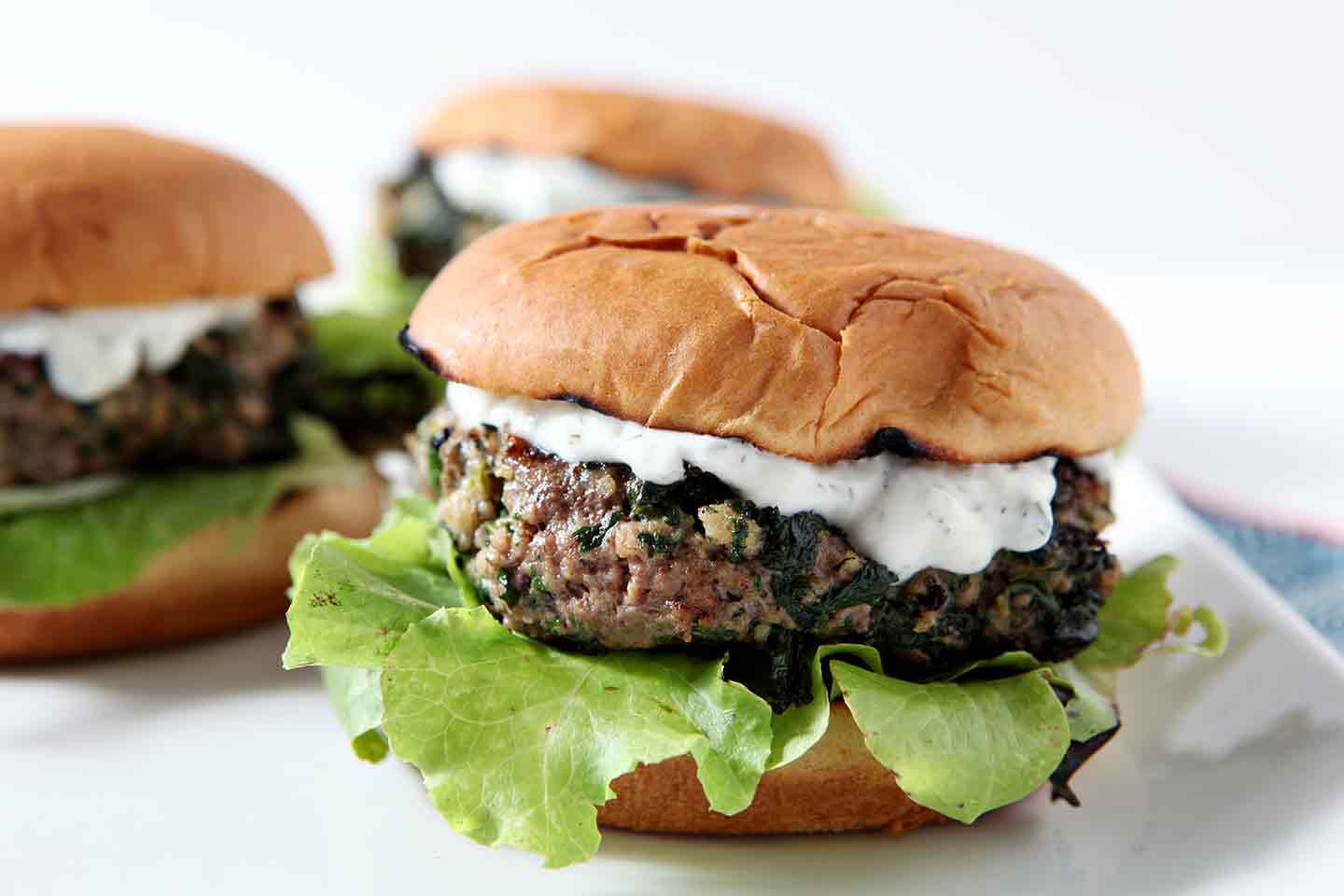 Three Spinach and Feta Burgers sit on a white platter, ready for consuming