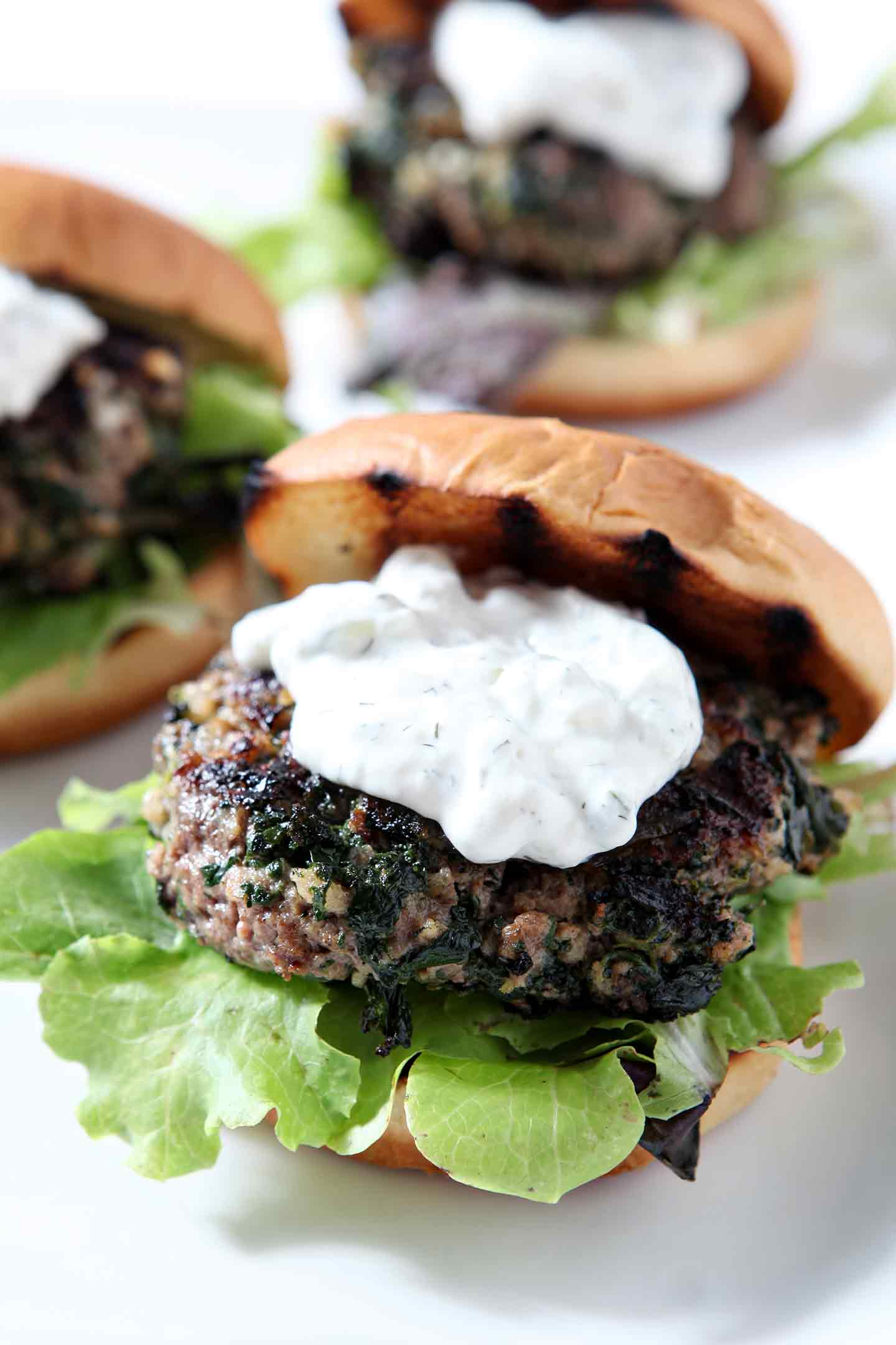 Close up of a burger, topped with tzatziki sauce