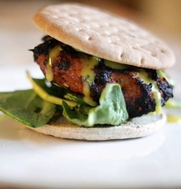 A Barbecue Turkey Burger on a thin bun with spinach and honey mustard dressing is served on a white plate