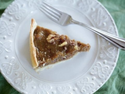 A slice of Fig Tart on a white plate with a fork