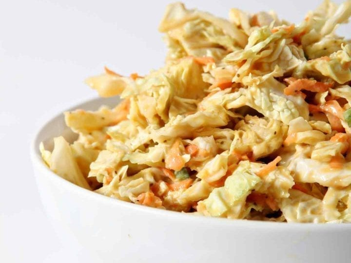 A bowl of No Mayo Honey Mustard Coleslaw sits on a white background.