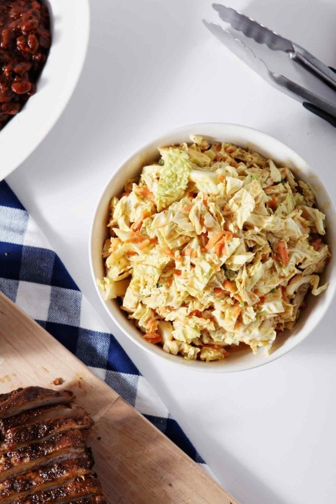 No Mayo Honey Mustard Coleslaw is served in a white bowl with other BBQ dishes