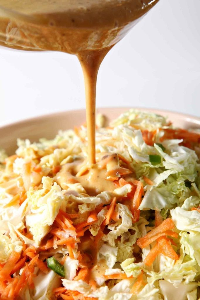 The dressing is drizzled on top of the No Mayo Honey Mustard Coleslaw.