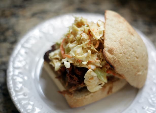 No Mayo Honey Mustard Coleslaw sits on top of a pulled pork barbecue sandwich, sitting on a white platter on a granite background