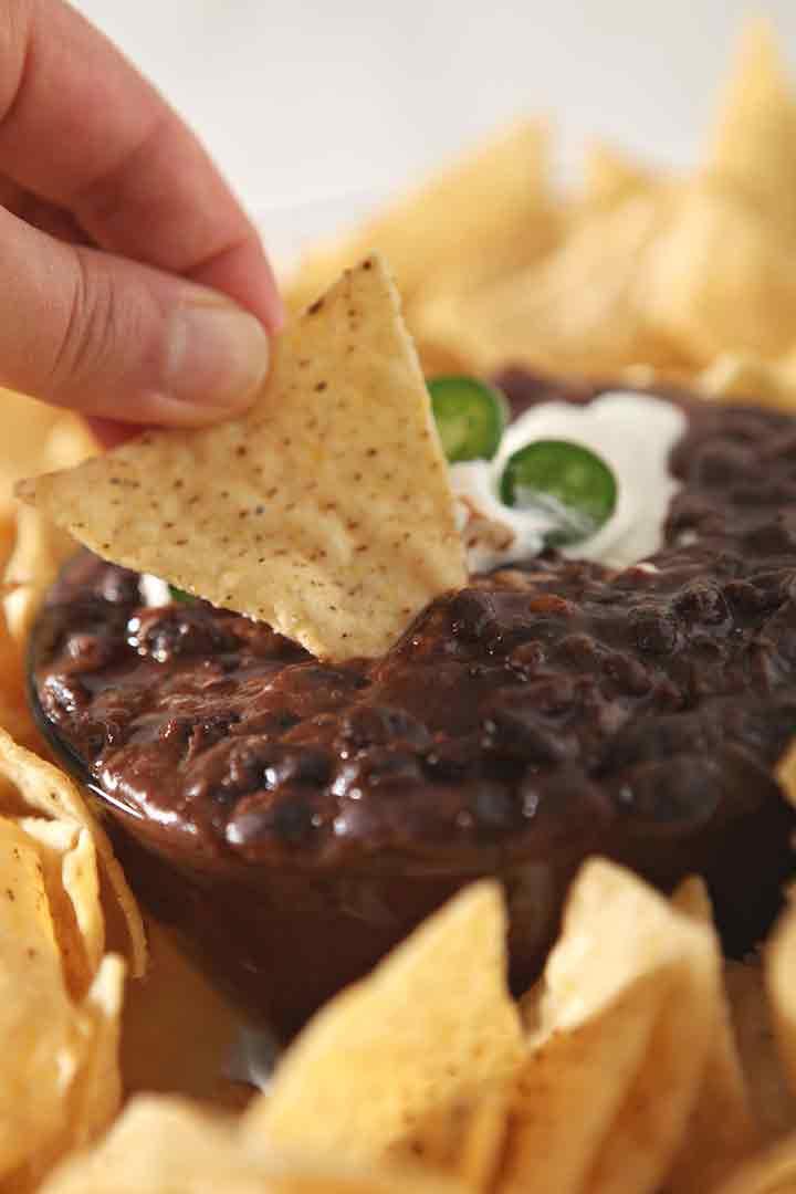 A woman dips a tortilla into Black Bean Dip, close up