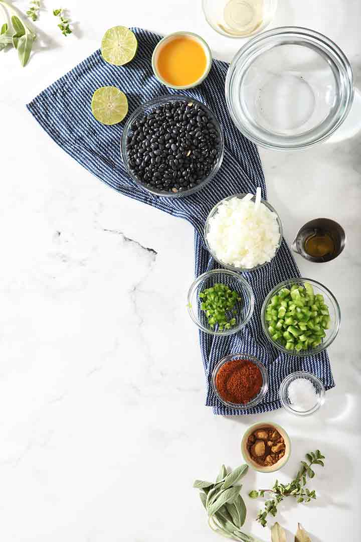 All the ingredients for Black Bean Dip are laid out on a marble surface in bowls before cooking
