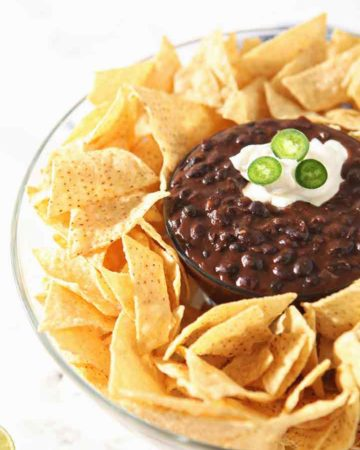 Black bean dip, garnished with sour cream and jalapeno slices, is shown in a bowl, surrounded by chips