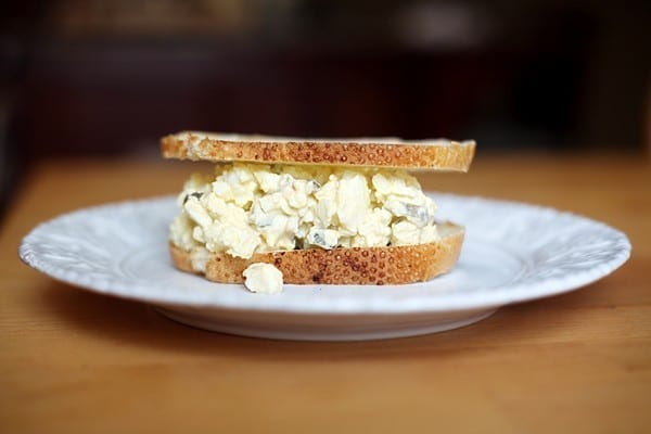 A close up of an egg salad sandwich on a white plate sits on a wooden table