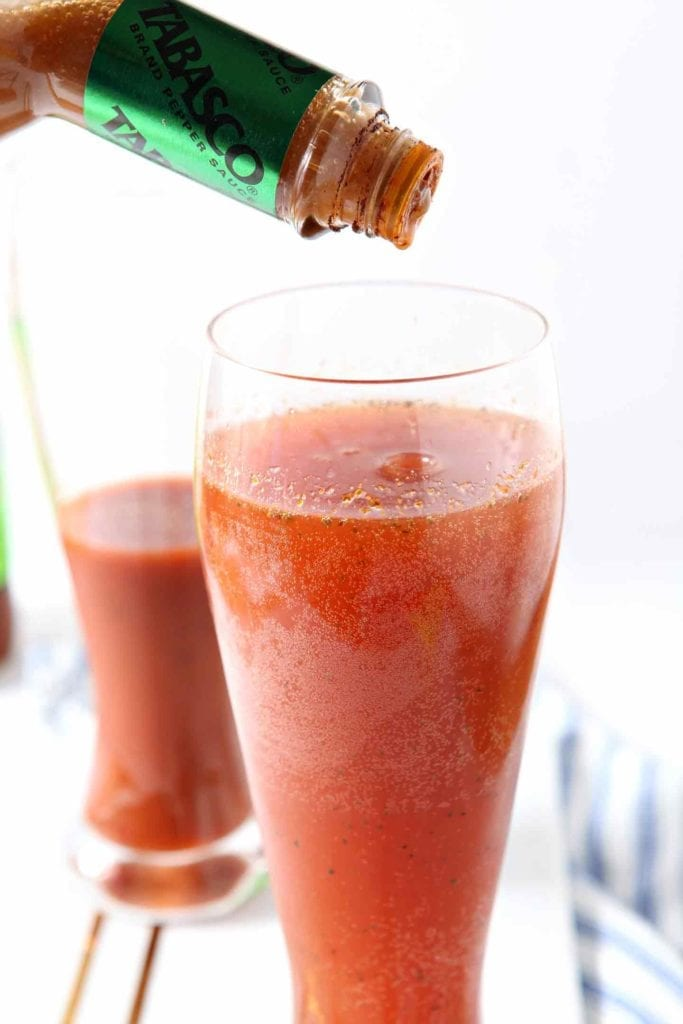 Tabasco sauce sprinkles into a glass of red beer