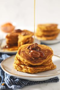 Syrup drizzles on top of a stack of Buttermilk Pumpkin Spice Pancakes with pecans on top