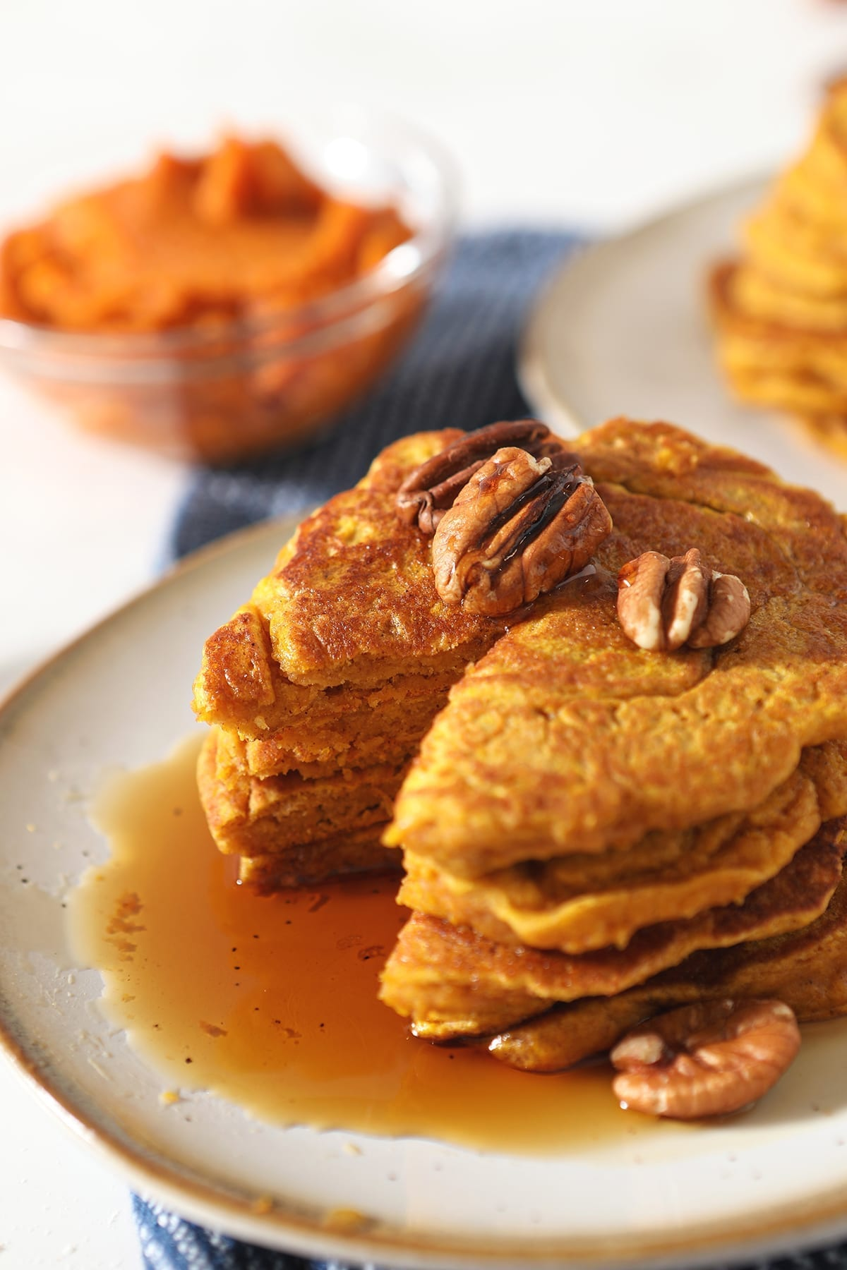 Close up of a stack of Buttermilk Pumpkin Spice Pancakes missing a triangular bite with syrup and pecans