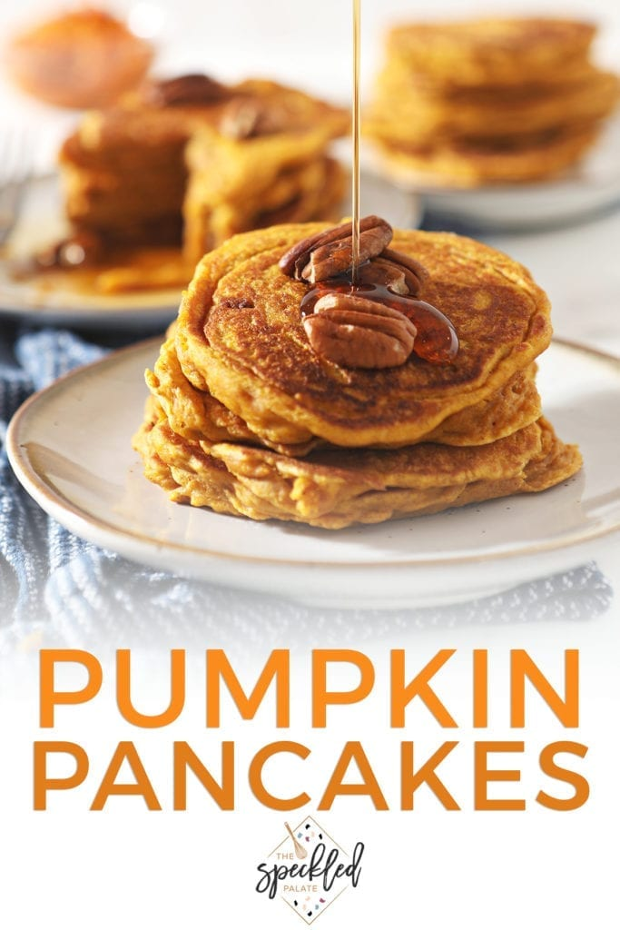 Syrup drizzles on top of a stack of Buttermilk Pumpkin Spice Pancakes with pecans on top with the text 'pumpkin pancakes'