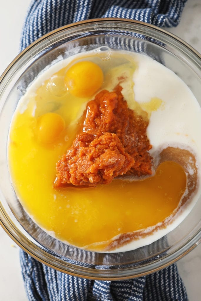 Pumpkin puree, buttermilk, eggs and other wet ingredients in a glass bowl on top of a blue towel