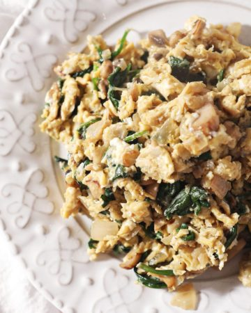 Close up of a serving of Scrambled Eggs with Spinach, mushrooms and onions on a white plate