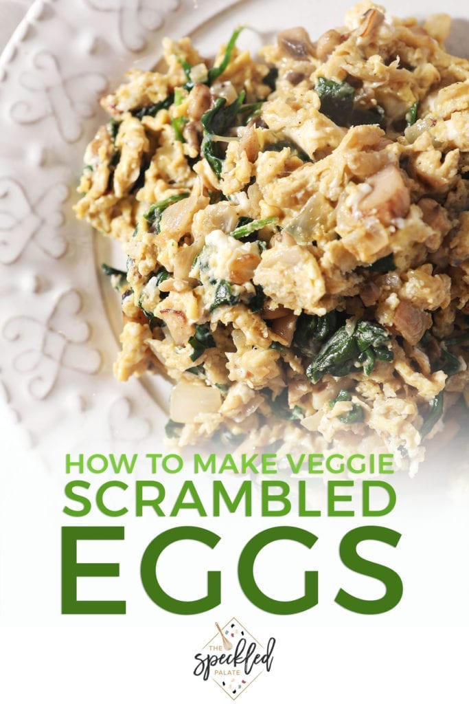 Closeup of a plate holding scrambled eggs with spinach, mushrooms and onions with the text 'how to make veggie scrambled eggs'
