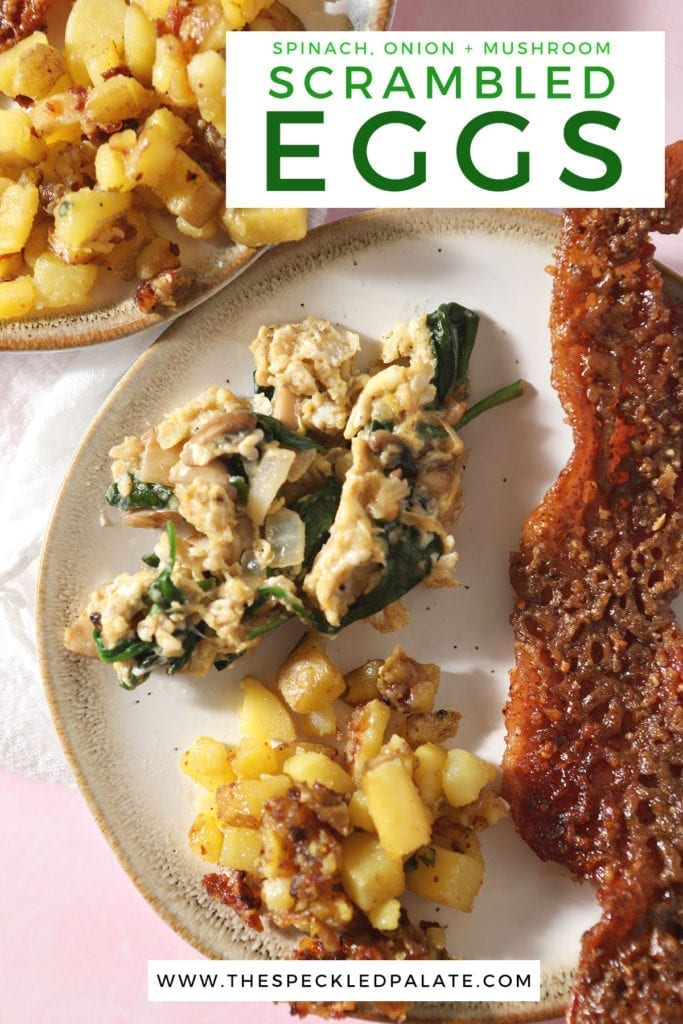 A serving of veggie scrambled eggs on a plate next to home fries and candied bacon with the text 'spinach, onion + mushroom scrambled eggs'
