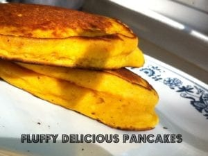 Two crusty, stacked Buttermilk Pumpkin Walnut Pancakes on a white decorative plate with text saying 'Fluffy Delicious Pancakes'