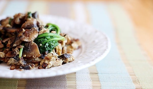 Scrambled eggs with mushrooms, spinach and more on a decorative white plate on a placemat