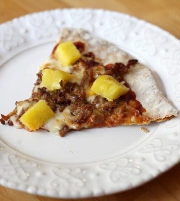 A slice of Pork and Pineapple Pizza on a white plate