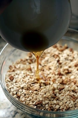 Maple syrup pouring into a glass bowl of granola ingredients