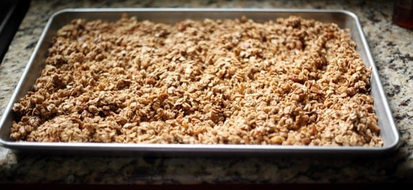 A baking sheet full of Homemade Maple Nut Granola on a granite countertop