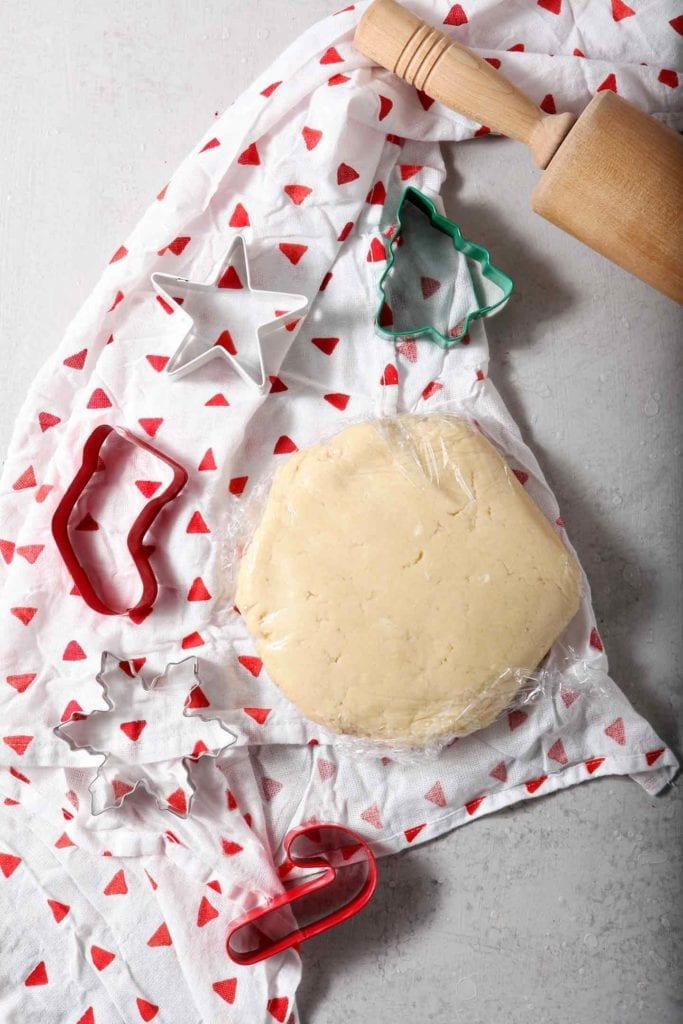 The refrigerated All-Butter Tea Cake Cookie Dough sits in a round, wrapped in plastic wrap, and surrounded by cookie cutters and a rolling pin