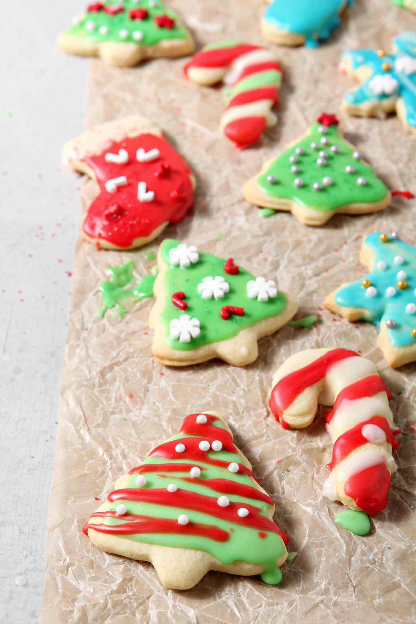 Iced and decorated All-Butter Tea Cake Cookies dry on a piece of parchment paper