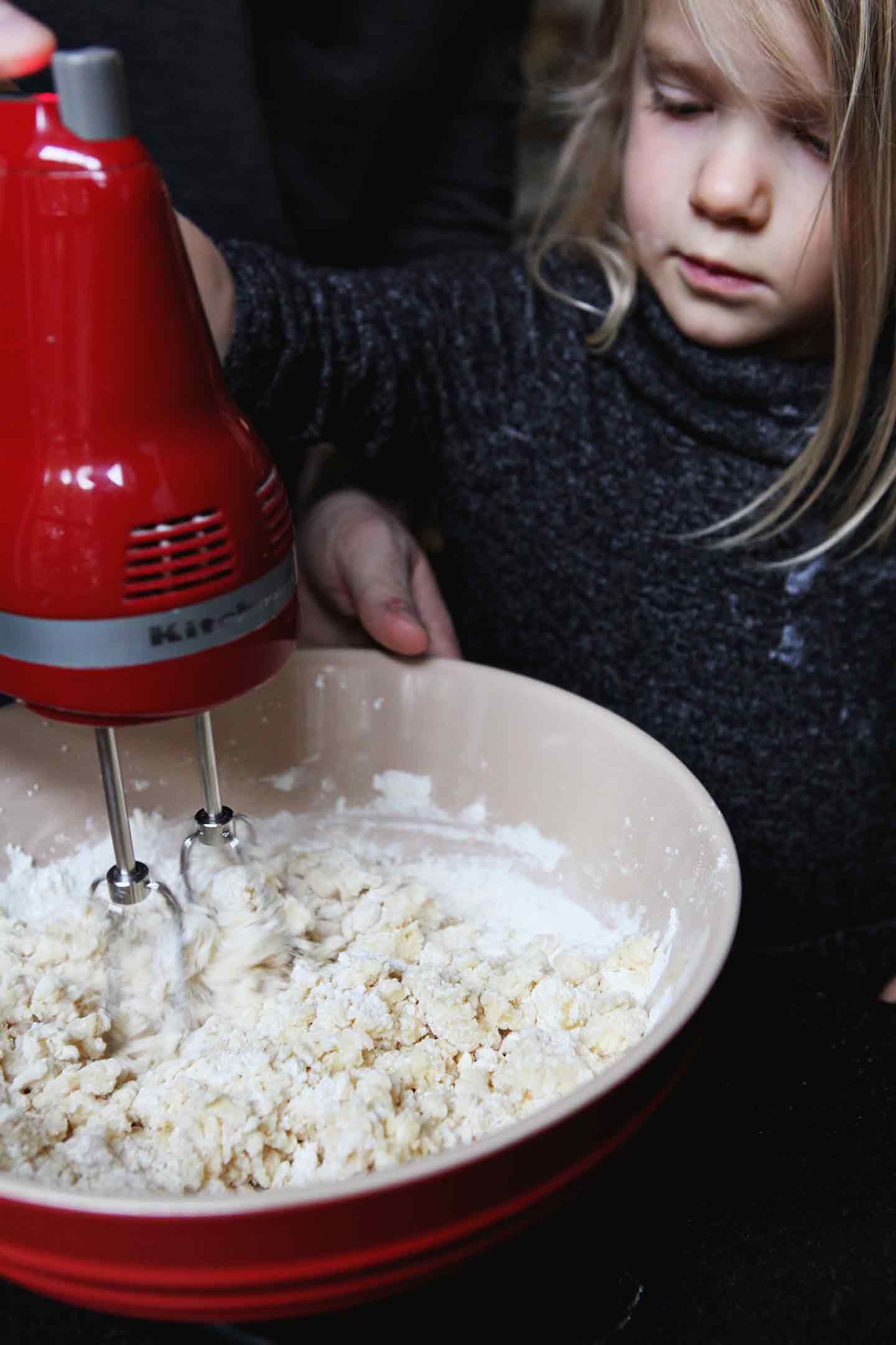 A man and a girl mix the batter for All-Butter Tea Cake Cookies using a hand mixer