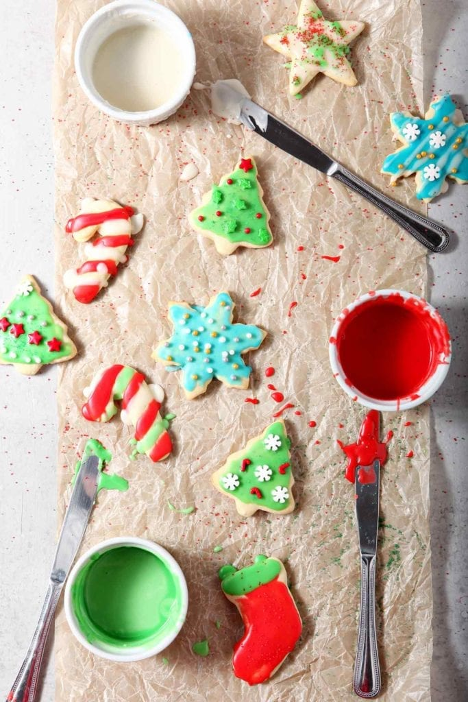 Overhead image of just-iced and decorated All-Butter Tea Cake Cookies drying on a piece of parchment paper, surrounded by decorating supplies