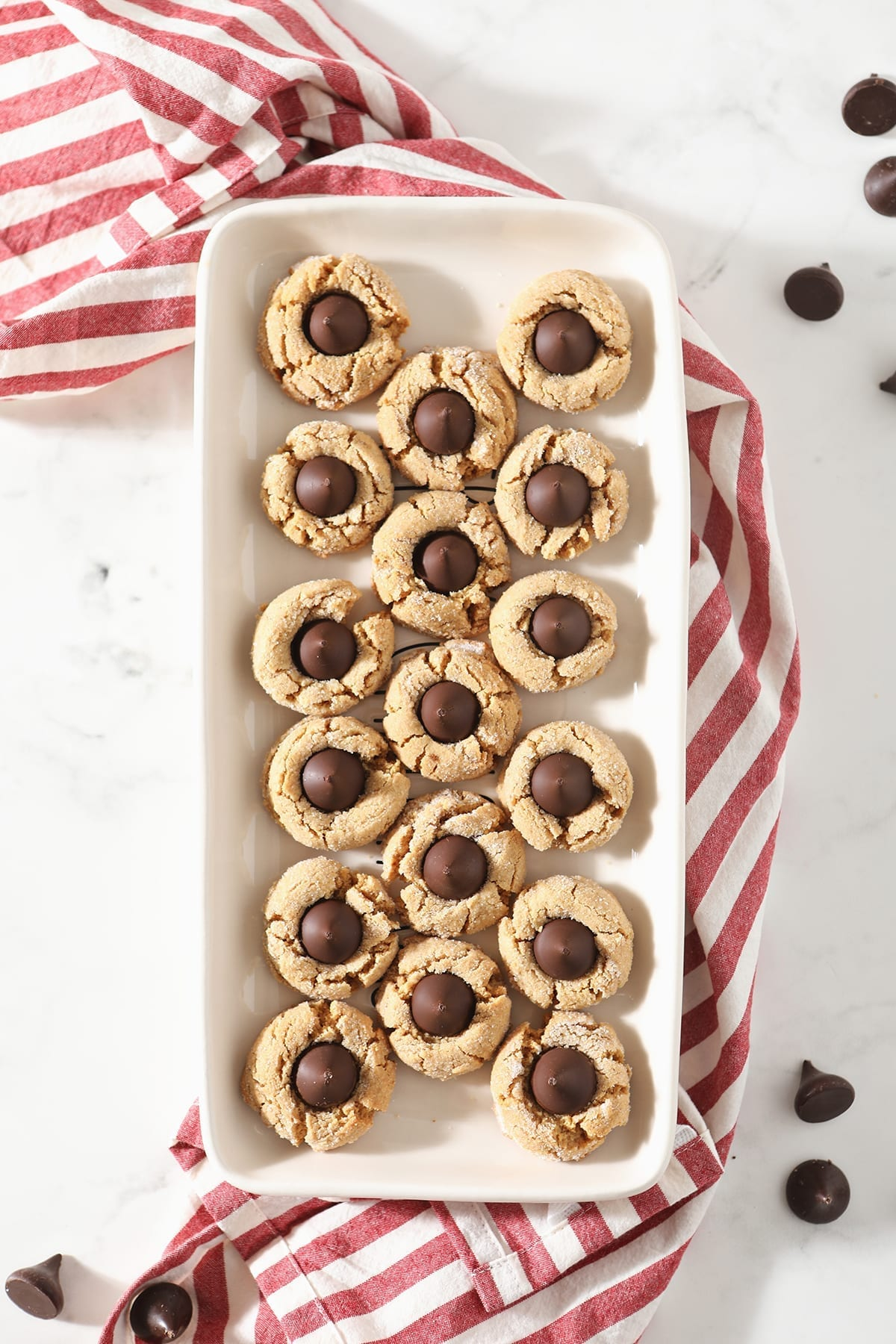 A tray of Dark Chocolate Peanut Blossom Cookies from above sitting on top of a red and white striped towel on a marble countertop