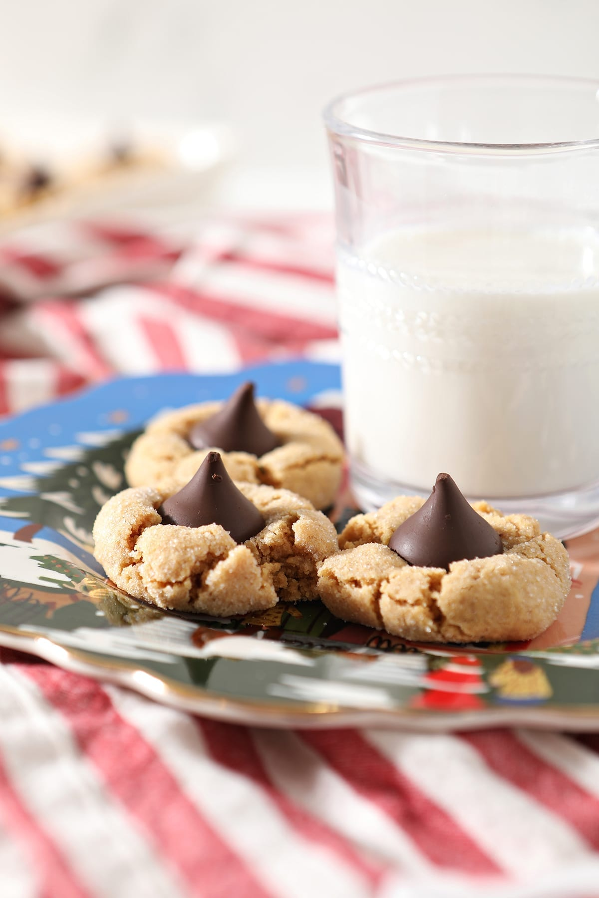 Three Dark Chocolate Peanut Blossoms sit on a blue painted plate next to a glass of milk on top of a red and white striped towel