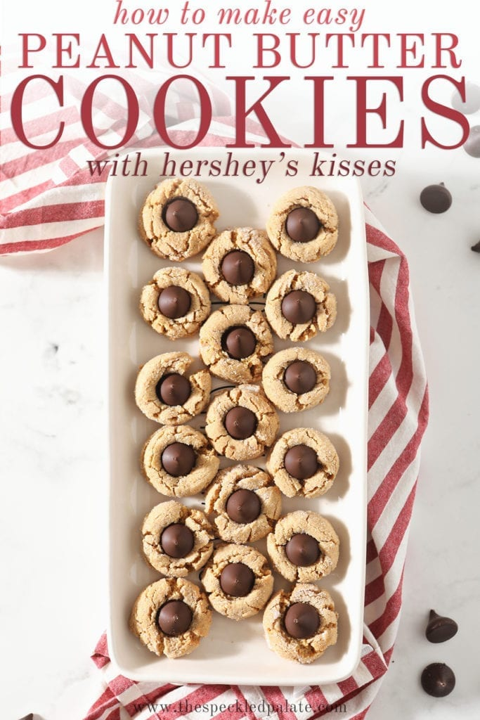 A tray of Dark Chocolate Peanut Blossom Cookies from above sitting on top of a red and white striped towel on a marble countertop with the text 'how to make easy peanut butter cookies with hershey's kisses'