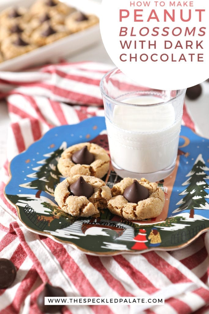 Three Dark Chocolate Peanut Blossoms sit on a blue painted plate next to a glass of milk on top of a red and white striped towel with the text 'how to make peanut butter blossoms with dark chocolate'