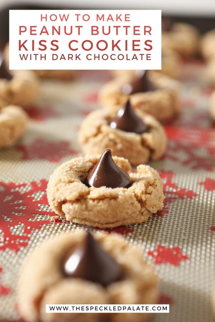 A row of baked peanut butter cookies with hershey's kisses on a sheet pan with the text 'how to make peanut butter kiss cookies with dark chocolate'