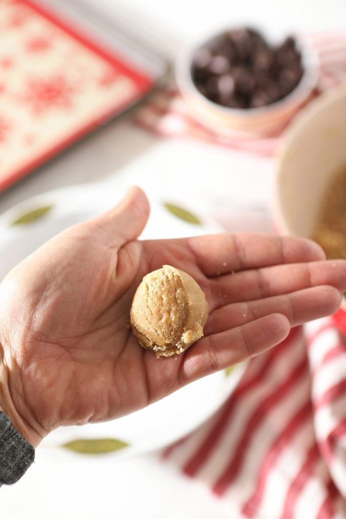 A hand holds a ball of peanut butter cookie dough