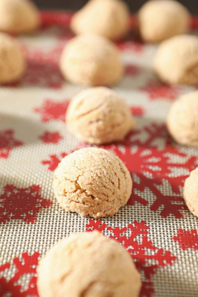 A festive red and white silat holds baked peanut blossom cookies before the Kisses are added