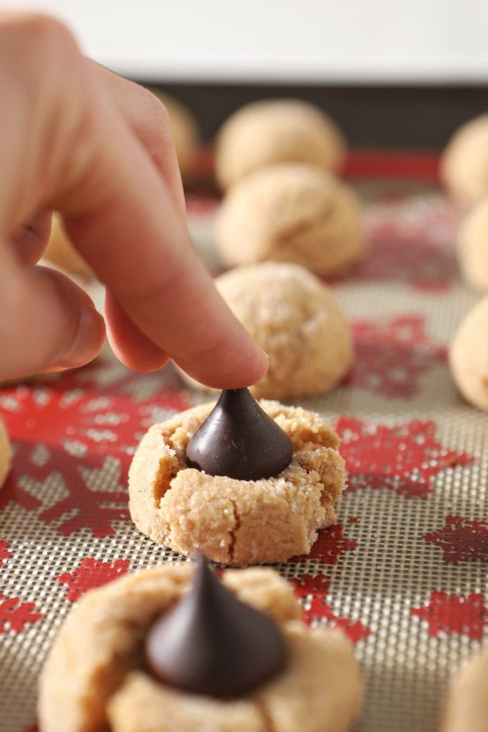 A hand presses a Dark Chocolate Hershey's Kiss into a peanut butter blossom