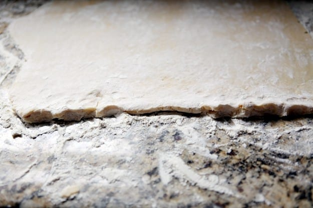 Close up of cookie dough rolled flat on a floured countertop