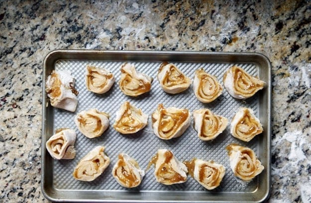 Sliced Fig Pinwheels on a metal baking pan before baking on a granite countertop
