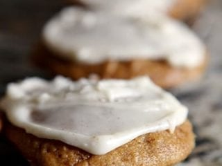 Close up of iced Pumpkin Drop Cookies on a cooling rack over granite