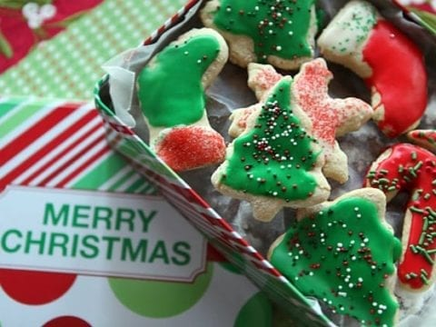 Iced and sprinkled Christmas trees, stockings, snowflakes and candy cane cookies in a red, white and green Merry Christmas cookie tin