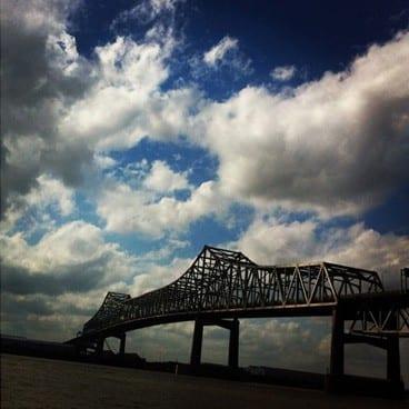 A blue cloudy sky behind a metal bridge over water