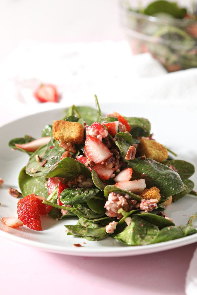 A strawberry spinach salad on a white plate tossed with strawberry vinaigrette