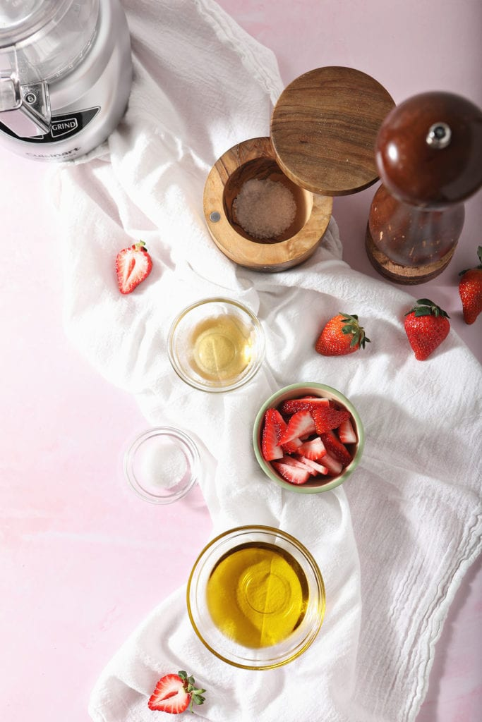 Ingredients for homemade salad dressing on a white cloth on top of a pink surface