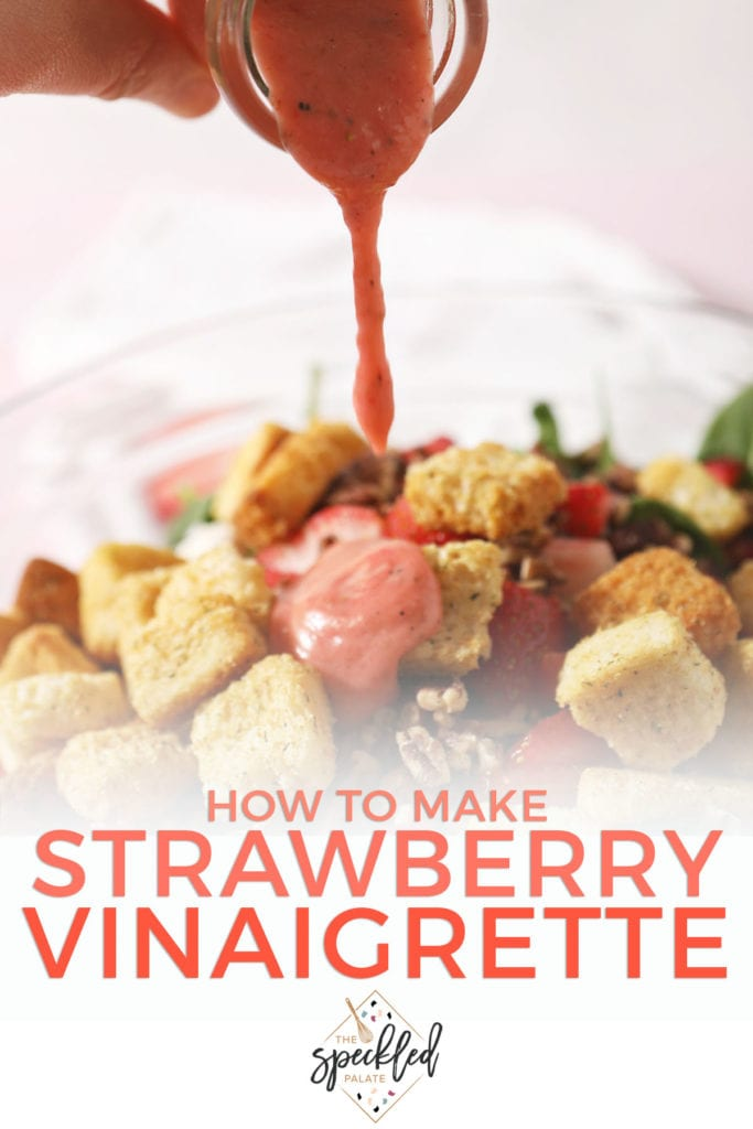 Strawberry salad dressing drizzles on top of a salad with croutons, cheese and more with the text 'how to make strawberry vinaigrette'