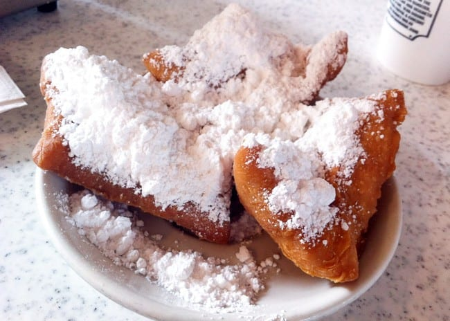 A white plate of three beignets coated in powdered sugar