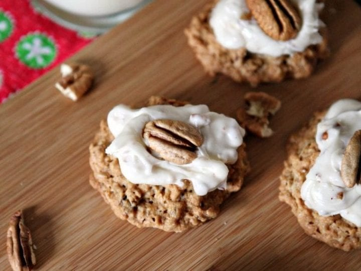 A wooden platter holds several Quebec Maple Pecan Drop Cookies, with a glass of milk sitting in the background