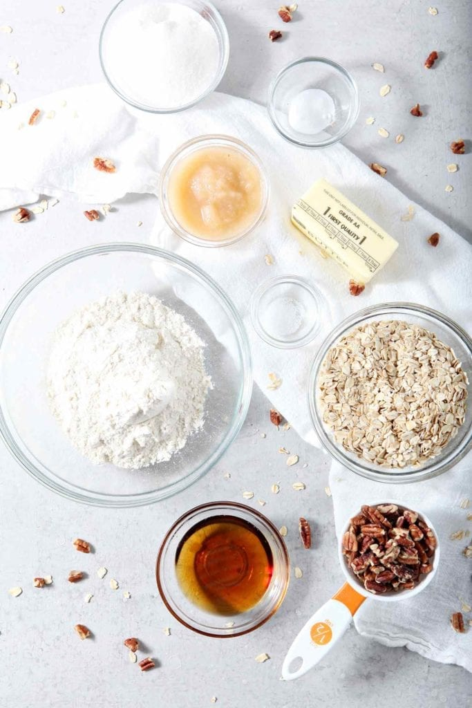 Ingredients for Quebec Maple Pecan Drop Cookies are laid out on a grey backdrop
