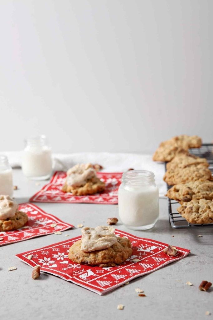 Several iced Quebec Maple Pecan Drop Cookies are served with small mason jars of milk