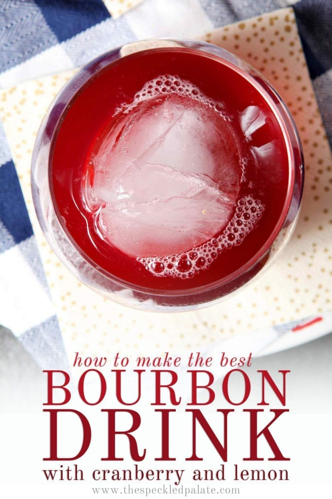 Close up of an old fashioned glass holding red liquid with the text 'how to make the best bourbon drink with cranberry and lemon'